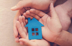 A pair of adult's hands holding a child's hands, holding a picture of a blue house.